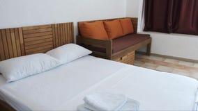 Гостиничный номер с белой двуспальной кроватью, коричневая софа с оранжевыми валиками и занавесы шоколада сток-видео