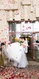 Гости бросая Confetti над женихом и невеста на свадьбу Стоковое Изображение