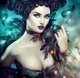 Готическая сексуальная молодая женщина halloween Красивая модельная девушка с макияжем фантазии в костюме goth с черными пер стоковая фотография rf
