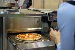 Готовая итальянская пицца на тонком тесте, свежем от печи, производственного оборудования orerator снимает видео- продукцию стоковое изображение