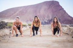 3 готового красивых девушек бегуна молодых для начала и для бега для трудных мероприятий на свежем воздухе разминки и фитнеса пос стоковые фотографии rf