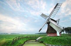 Голландская ветрянка во время пасмурного утра лета Стоковые Фото