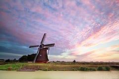 Голландская ветрянка каналом во время восхода солнца Стоковое фото RF