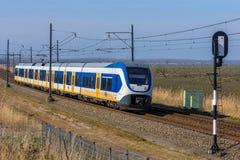 Голландский электропоезд путешествуя через сельскую местность стоковые изображения rf