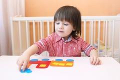 2 года ребенка сделали скалозуба бумажных деталей дома Стоковое фото RF