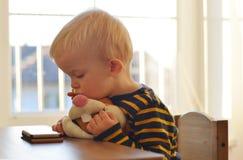 2 года старого мальчика наблюдают на мобильном телефоне и держат его зайцев плюша Стоковая Фотография RF