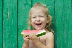 2-год-девушка смеясь над и держа арбузом Стоковая Фотография