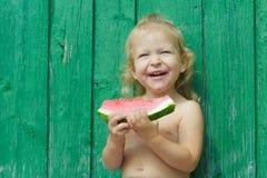 2-год-девушка смеясь над и есть арбузом Стоковые Фотографии RF