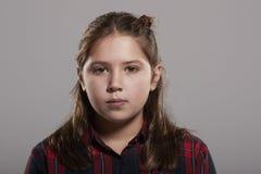 10 годовалая девушка смотря к камере, головы и плечи Стоковые Фото