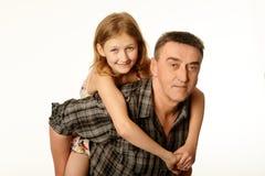 Годовалая дочь 12 обнимая ее отца сидя на его назад Стоковое фото RF