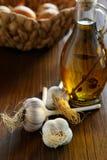 Голова бутылки чеснока и оливкового масла на таблице Стоковая Фотография