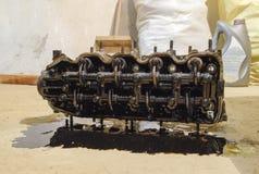 Голова блока цилиндров Голова блока цилиндров, который извлекли от двигателя для ремонта Части в масле двигателя Ca Стоковое Фото