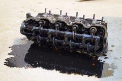 Голова блока цилиндров Голова блока цилиндров, который извлекли от двигателя для ремонта Части в масле двигателя Ca Стоковое фото RF