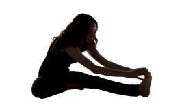 Голова к представлению колена в йогу в силуэте стоковая фотография