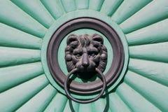 Голова новичка льва держа ручку двери в его рте, парадном входе Стоковое Изображение