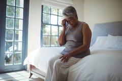 Голова расстроенной старшей женщины касающая дома Стоковые Фото