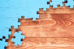 Головоломка на коричневой деревянной предпосылке Стоковые Фото