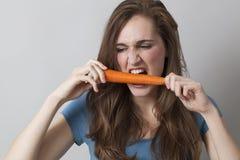 Голодная девушка 20s сдерживая морковь с энергией стоковая фотография
