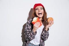 Голодные смеясь над фраи и бургер удерживания женщины Стоковые Изображения RF