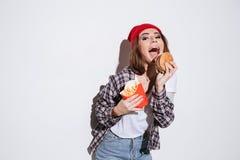 Голодные эмоциональные фраи и бургер удерживания молодой женщины Стоковые Фото