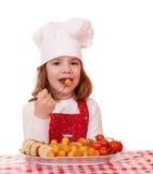 Кашевар маленькой девочки ест еду лакомки Стоковая Фотография