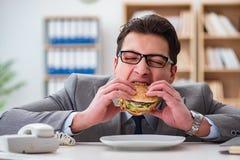 Голодный смешной бизнесмен есть сандвич высококалорийной вредной пищи стоковое изображение