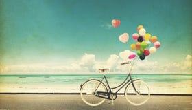 Год сбора винограда велосипеда f с воздушным шаром сердца на небе пляжа голубом Стоковые Изображения RF