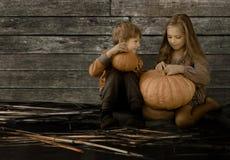 Год сбора винограда, дети ретро тип Довольно белокурая девушка и мальчик сидя рядом с большими тыквой и беседой Стоковое Фото