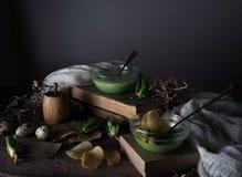 Год сбора винограда, Провансаль суп шпината в стеклянном шаре на грубой деревенской таблице обломоки, яичко триперсток стоковое фото