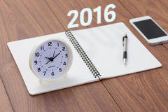 Год 2016 с тетрадью и часами на деревянной таблице Стоковая Фотография