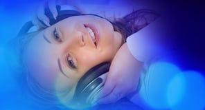 Голубая абстрактная предпосылка, молодая женщина в наушниках слушая к музыке Стоковые Изображения