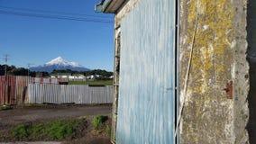Голубая дверь фермы с Mt Taranaki в предпосылке Стоковое фото RF