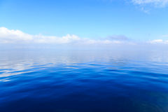 Голубая вода океана с облаками на заднем плане Стоковые Изображения RF