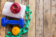 Голубая гантель, белое полотенце, измеряя лента и красное яблоко на древесине Стоковые Изображения