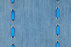 Голубая лента сатинировки введенная в кольца золота на джинсовой ткани Стоковые Изображения RF