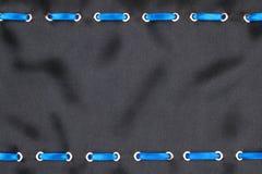 Голубая лента сатинировки введенная в кольца золота на черном шелке Стоковое Изображение RF