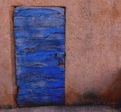 Голубая деревянная дверь врезанная в красной стене в Roussillion Стоковые Фотографии RF