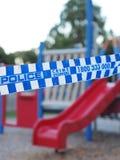 Голубая и белая полиция связывает cordoning тесьмой с красочного района спортивной площадки как место преступления Стоковая Фотография