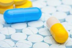 Голубая и желтая пилюлька на голубых медицинских таблетках Стоковые Изображения RF