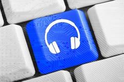 Голубая кнопка наушников на клавиатуре Стоковые Фотографии RF