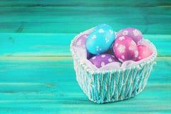 Голубая корзина в форме сердца с пасхальными яйцами деревянное предпосылки голубое пасха счастливая Стоковая Фотография RF