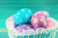 Голубая корзина в форме сердца с пасхальными яйцами деревянное предпосылки голубое пасха счастливая Стоковые Фото