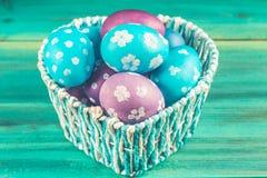 Голубая корзина в форме сердца с пасхальными яйцами деревянное предпосылки голубое пасха счастливая Стоковые Фотографии RF