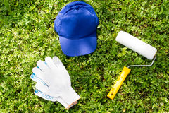 Голубая крышка, ролик краски и белые работая перчатки на зеленой траве Стоковая Фотография