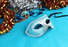 Голубая маска масленицы на голубой предпосылке с праздничными украшениями Стоковые Изображения