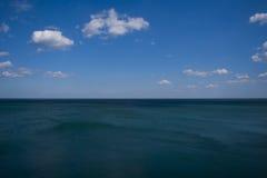 Голубая морская вода и голубое небо с облаками Стоковые Изображения RF