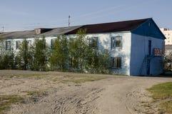 Голубая нищета и плохое 2-storeyed здание с деревьями вокруг Стоковые Изображения