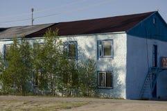 Голубая нищета и плохое 2-storeyed здание с деревьями вокруг Стоковые Фотографии RF