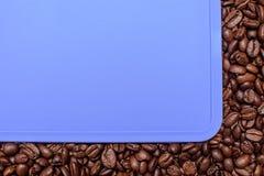 Голубая предпосылка вокруг краев зажаренных в духовке кофейных зерен, космос для текста Стоковые Фото