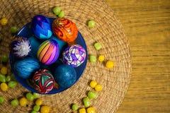 Голубая плита с пестроткаными пасхальными яйцами, конфетами, предпосылкой соломы Стоковые Изображения RF
